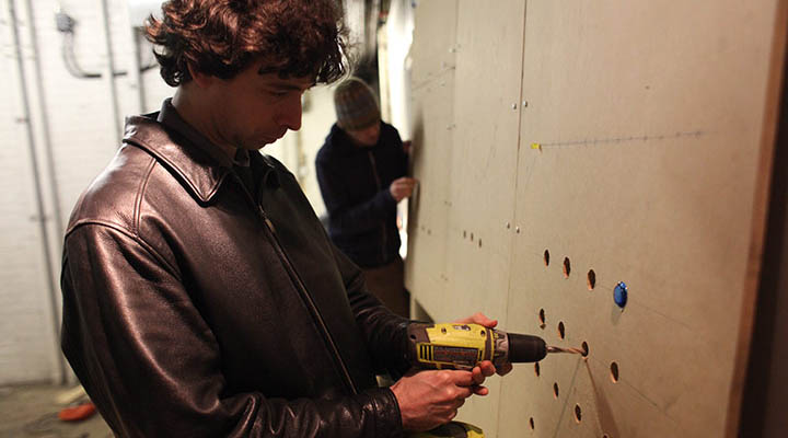 Nick drilling holes into cupcake machine wall. Photo by Ida Benedetto.